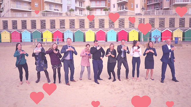A group of happy employees on Bournemouth beach with brightly colored beach huts behind them